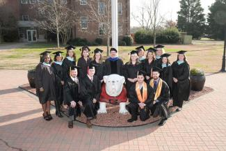 Fall 2017 Graduates posing with UGA statue