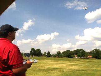 "Clay Bennett ""pilots"" an aerial drone over turfgrass research plots"