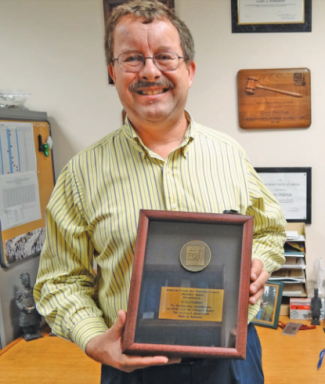 Dr. Gary Pederson holding his AFGC Medallion Award