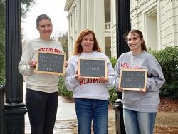 Photo of Allison (left), Becky (center), and Mady (right) holding signs listing individual UGA degrees