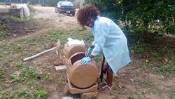 Esther Akoto working with composting barrels