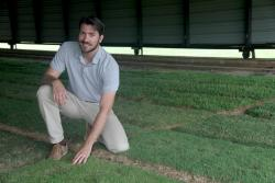 David Jesperson poses with his turfgrass research plots