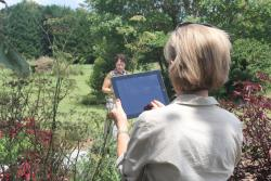 Photo of Master Gardner  holding iPad to take photos of insects