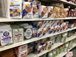 Photo of various bags of flour on a grocery store shelf