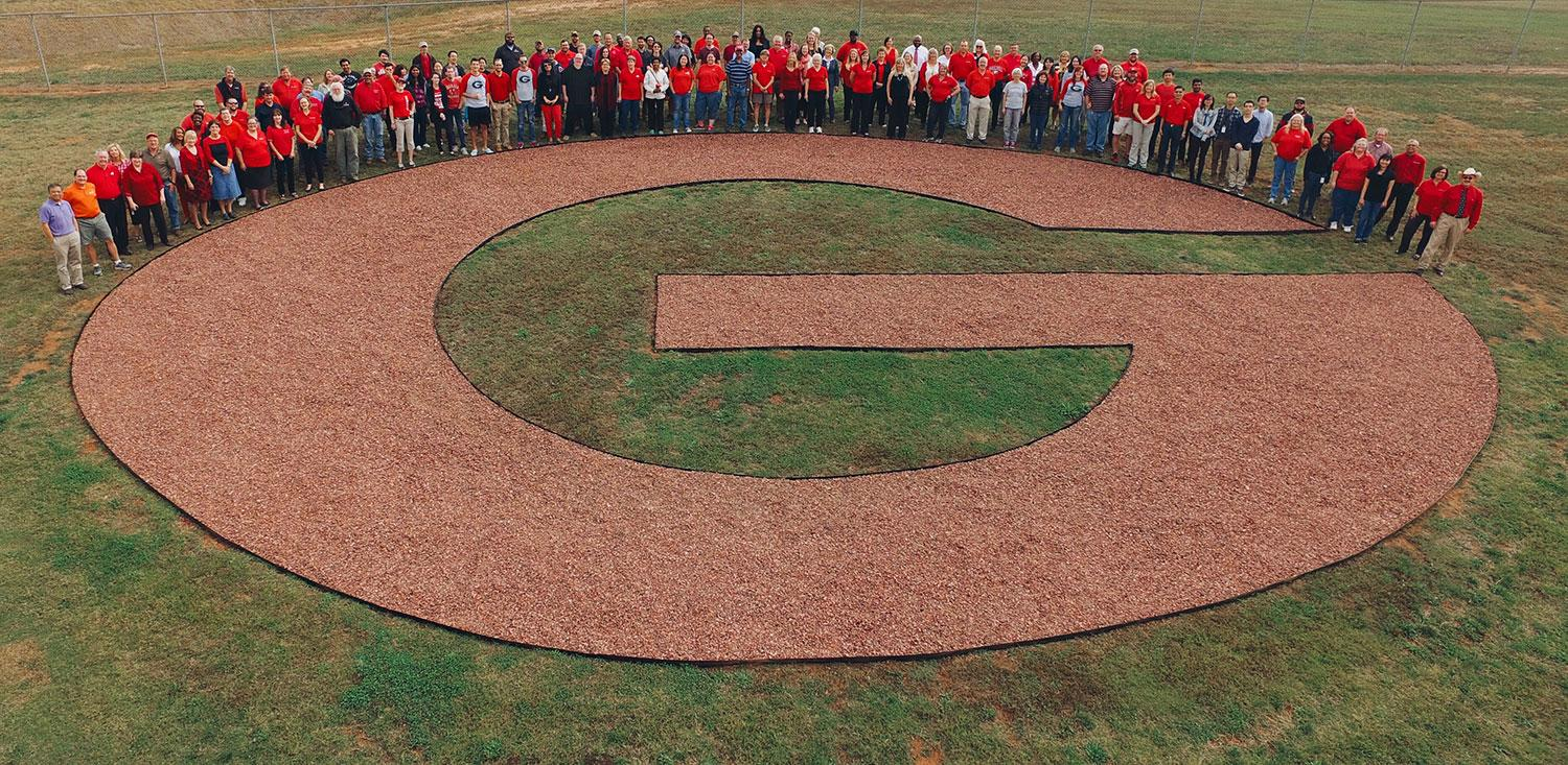 Faculty and staff from UGA-Griffin gather around the Big G at the edge of campus