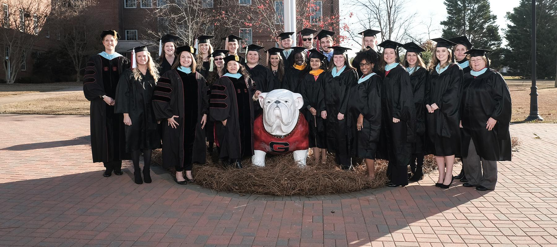 The UGA-Griffin graduating class of Fall 2016 pose with Dr. Lew Hunnicutt and the Uga statue near the Flynt Building