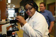 A student participant of the Young Scholars Program uses a microscope in a lab at UGA's main campus